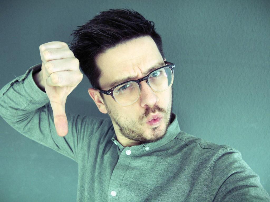 The Wollium macht Thumbs Down mit grauem Hemd vor grauer Tapete.